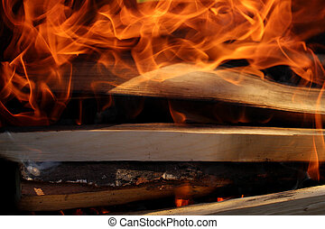 Flames on wood in dark - Charred wood and bright flames on...