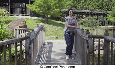 young woman walking on suspended wooden bridge in park