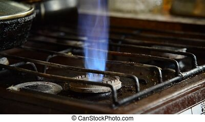 Flames from a gas burner on old kitchen stove