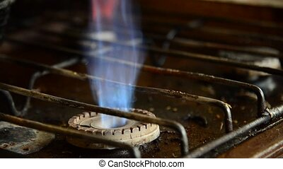 Flames from a gas burner on old kitchen stove - Flames from...