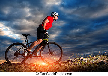 mountain bicycle rider on the hill with sunrise background -...