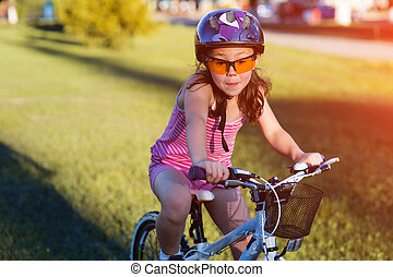 Child riding a bicycle. The kid in helmet on bike