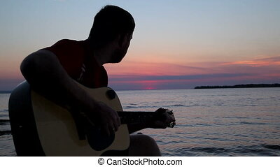 boy plays on guitar at sunset HD