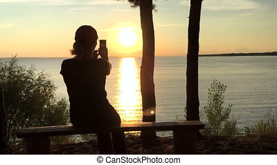 a young girl removes the sunset on the telephone. Slow...