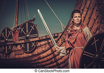 Viking woman with sword and shield standing near Drakkar on...