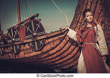 Viking woman standing near Drakkar on the seashore -...