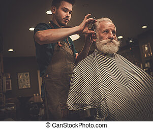 Confident senior man visiting hairstylist in barber shop. -...