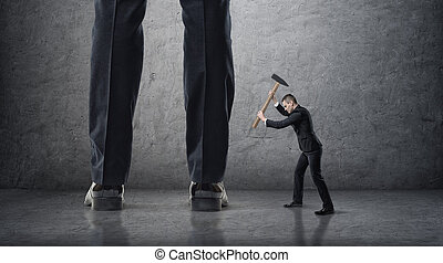 Small businessman hitting giant legs of another with hammer