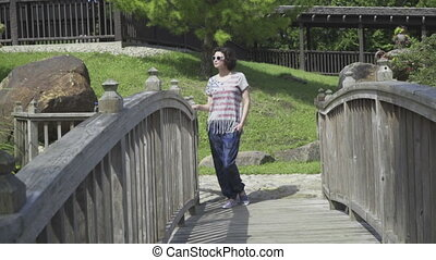 young woman walking on suspended wooden bridge