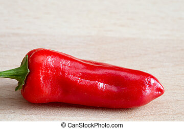 Red chilli pepper 'capsicum annuum' on a wooden chopping...