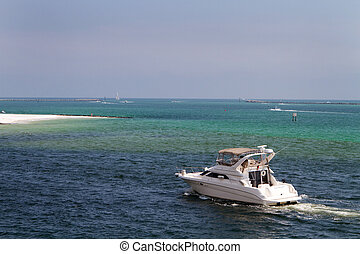Boating In Destin Pass - Cabin cruiser motors through the...
