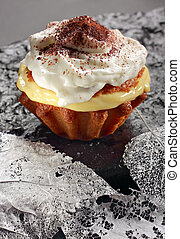 Muffin with pudding filling and whipped cream on black...