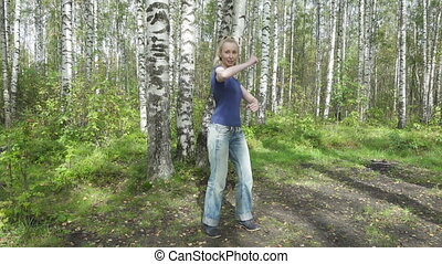 The young slender woman does sporting training in park. Slow...