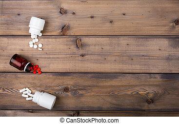 Setup from various pill bottles an blister pack on wooden...