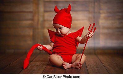 funny baby in devil halloween costume on wooden background -...