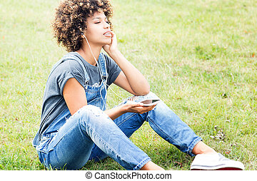 Young girl listening to music in park, relaxing - Young...