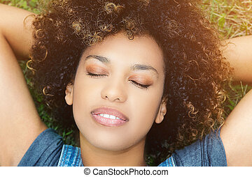 Young african girl relaxing in park.