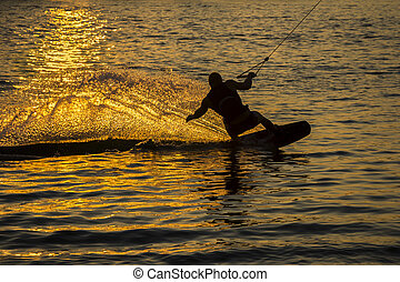Silhouette Wakeboarder in action on sunset