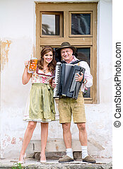 Couple in traditional bavarian clothes with beer and...