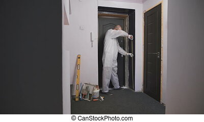 Worker in overalls, takes measurements of the doorway, he...