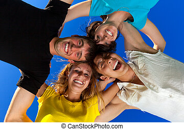 The four friends, embracing, has formed a circle and bent...