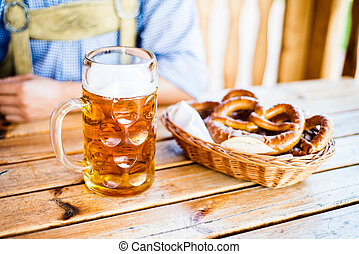 Man in traditional bavarian clothes with beer and pretzels -...