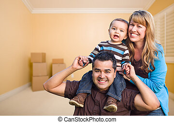 Young Mixed Race Family In Room With Moving Boxes