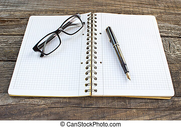 Fountain pen and spiral notebook with eyeglasses on wooden...
