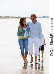 Couple on a beachwalk - Attractive young couple walking...