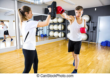 Two dedicated people training boxing at the fitness gym