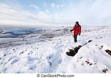 Indian woman hiking in winter snow, Peak District, UK