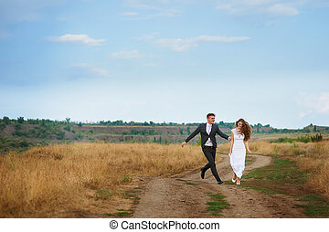 Groom catches bride on the summer field.