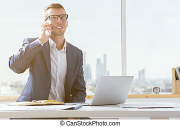 Young businessman on phone - Handsome young businessman in...
