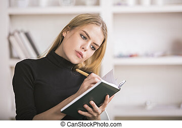 Woman taking notes in diary - Attractive european woman...