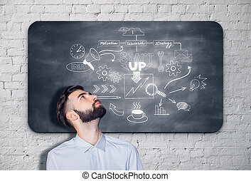 Start up concept - Young bearded businessman looking up at...