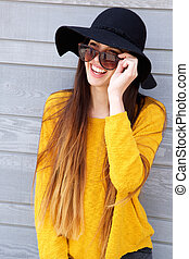 Trendy young woman wearing sunglasses and hat - Portrait of...