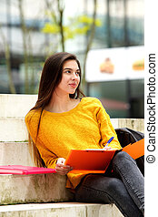 College student sitting on steps with notebook