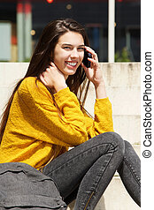 Smiling female student talking on mobile phone