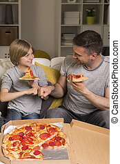 Its pizza time - Shot of father and son eating pizza in a...