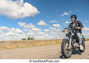 Young man riding his motorbike on open road - Ready for any...
