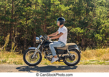 Young man riding his motorbike on open road - Adventuring...
