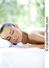 Beautiful woman is resting on spa bed