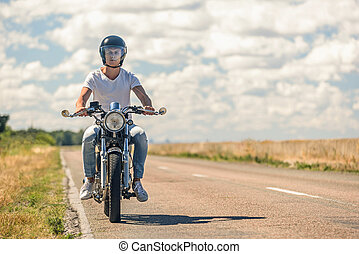 Young man riding his motorbike on open road - Borning to...