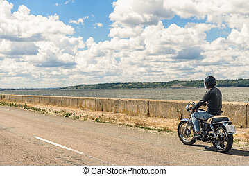 Young man riding his motorbike on open road