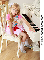 Girl playing the piano - Cute little blonde girl sitting...