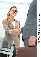 Business partners shaking hands in the modern office - Happy...
