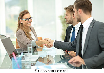 Happy business partners shaking hands in an office - Happy...