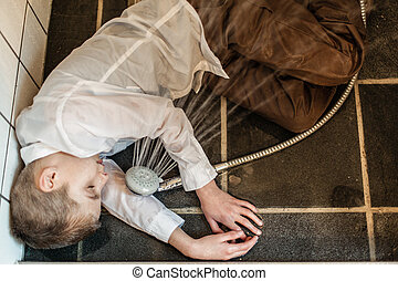Overhead view of boy passed out in bathroom - Overhead view...