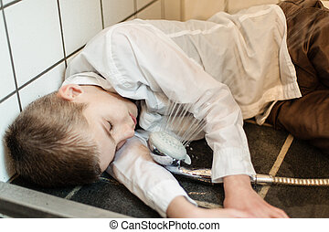 Fully clothed boy unconscious on shower floor beside...