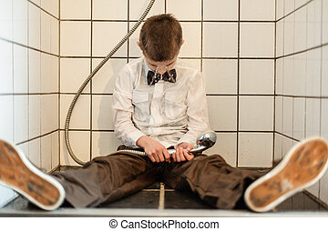 Unconscious boy holding running shower head wearing bow tie...